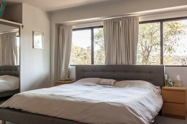 Minimalist bedroom with white bedding and a gray tufted headboard. White dresser night stands are on each side. Gray curtained windows.