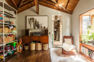 Craft Storage in Living room with lounge chair, sheepskin thrown, rug, shelves with baskets and toys, baskets on floors, credenza, stereo, wood floors, records, arched wood ceiling.