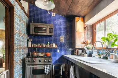 A kitchen with a wood ceiling, gray counter, and wood cabinets. Walls with blue tile and traditional geometric tile.