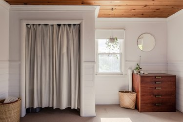 A sunlit bedroom with a curtain divider, hanging plant, wood dresser, round mirror, and baskets.