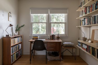 Wood office desk surrounded by bookshelves and shelves of books. Houseplants decorate the space. A printer is on a small table.