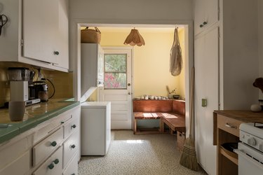 Kitchen with white cabinets and green-neutral tile counter. A wood bench with pottery and a floral shape pendant light.