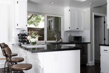 A kitchen with white cabinets, black counters, white tile backsplash, and wood bar stools. A wine rack and flowers, on a counter.
