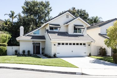 A white suburban house with a small patch of green grass