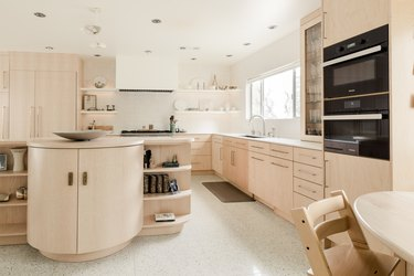 Minimalist kitchen with a curved kitchen island, beige wood cabinets, and speckled flooring.