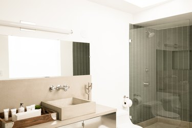 Bathroom with a square sink basin and facet fixed to a wall. A fluorescent bar light above. Shower with glass door and gray wall tiles.