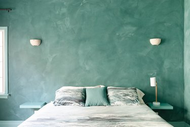 green plaster walls in bedroom with green bedding