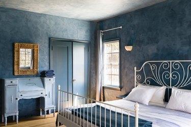 Bedroom with blue walls, white spiral bed frame, blue bedding, vintage blue desk, vintage gold mirror, bi-fold door, and curtained window.