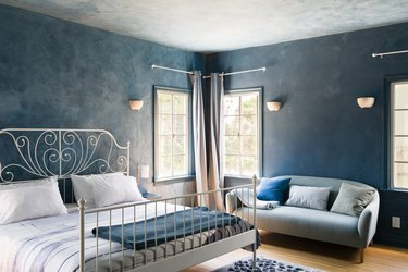 Blue wall bedroom with white spiral bed frame, wall sconces, blue couch, pillows, windows, and wood floor.