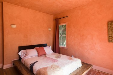 Bedroom with orange walls, white wall sconces, orange begging and pillows, orange curtains, and dark wood floor.