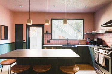 Kitchen with pink walls, green cabinets, gray counters, pink tile backsplash, bell pendant lights and wood floor.