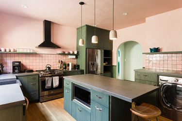 Kitchen with pink walls, green cabinets and shelves, gray counters, pink backsplash, and bell pendant lights.