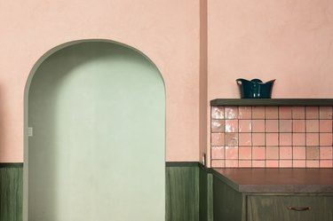 Pink kitchen wall with a pink square tile backsplash, green cabinets, and a green shelf. An arched doorway leading to a light green wall.