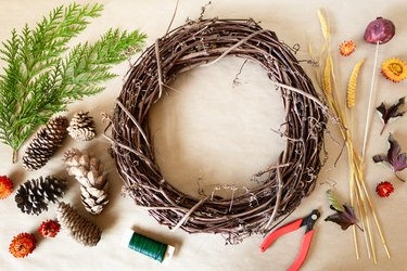 millet stems, cedar branches, wire, wire cutters, dried flowers, pine cones, and a dried pomegranate surround a grapevine wreath base