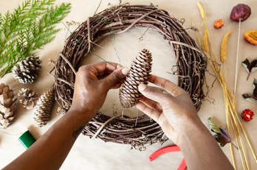 attaching a pine cone to a grapevine wreath base with wire