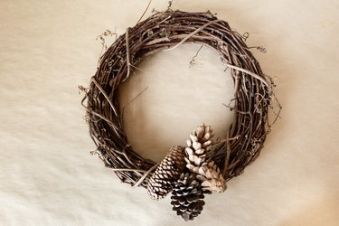 pine cones attached with wire to a grapevine wreath base