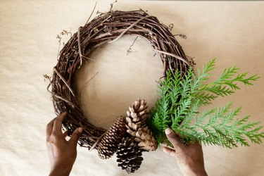 attaching cedar branches to a grapevine wreath