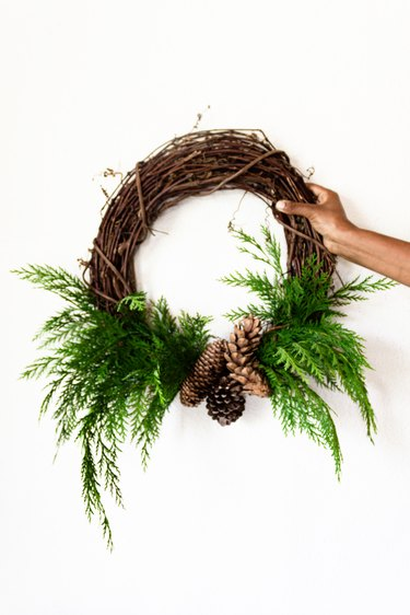 cedar branches and pine cones are attached to a grapevine wreath base
