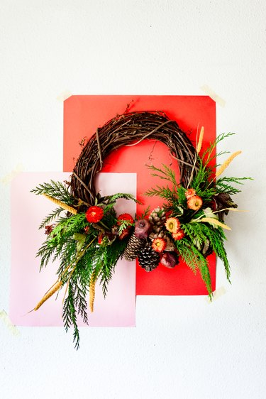 a holiday wreath made with cedar branches, pine cones, dried flowers, and dried pomegranates