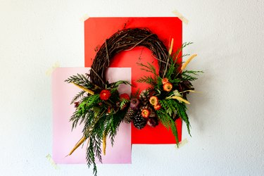 fall wreath made with cedar branches, pine cones, dried flowers, and dried pomegranates