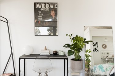 a vintage david bowie poster above a small, simple black metal desk