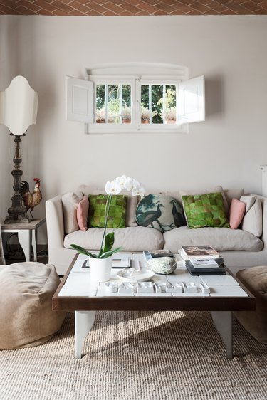 White love seat with green throw pillows under small window with white shutters