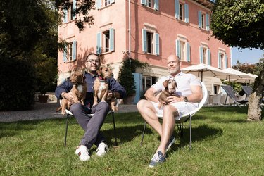 Two men sitting outside holding their dogs on their laps