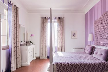 Lavender bedroom with upholstered headboard and lavender striped wallpaper
