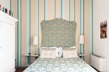 Green and cream bedroom with upholstered headboard and striped wallpaper