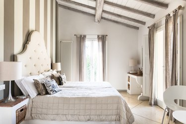 Neutral bedroom with ivory fabric headboard and large windows