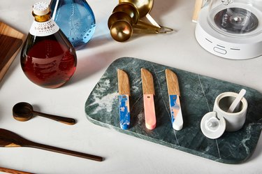 Marble cutting board with knives, spice jar, wood spoons, bourbon, gold measuring spoons