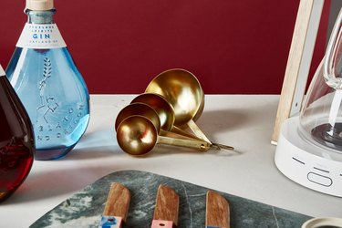 Gold measuring spoons with bottle of gin, marble cutting board, knives, and coffee maker