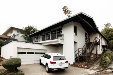 White home with large overhanging eaves with white car in driveway