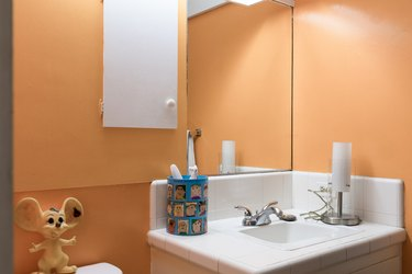 orange walls and mirror in small bathroom