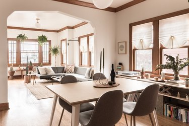 minimalist dining room with wood table, pendant lamp and grey Eames chairs
