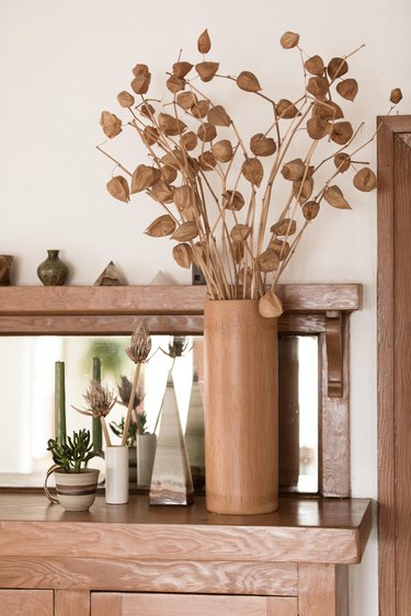 beige vase with dried flowers on a wooden tabletop