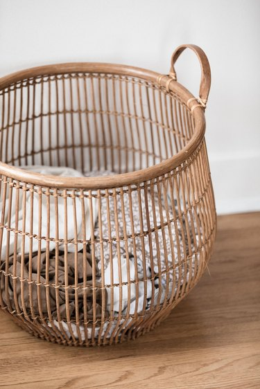 large wooden basket filled with laundry