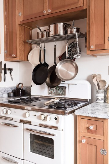 pans hanging over gas stove in a minimalist kitchen