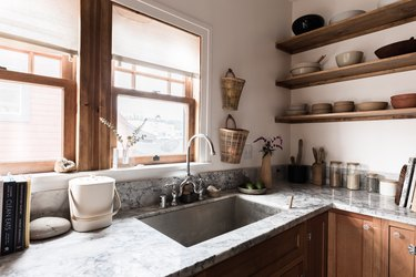 farmhouse sink with grey marble countertops and wood shelves