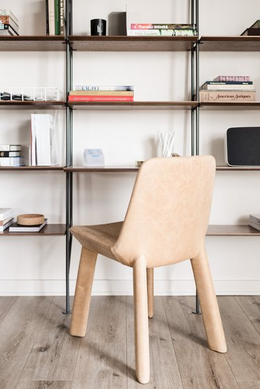 A peach-colored chair covered in soft material sits in front of a tall minimalist shelving unit