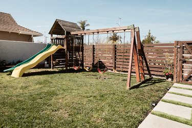 A wooden swing set on top of a patch of grass; a wooden horizontal fence and square concrete pavers