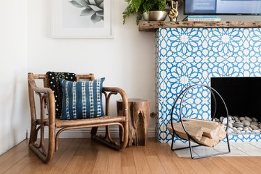 Boho chair, with a Shibori pillow, black-white patterned blanket, and a Moroccan star tile, wood mantel fireplace.