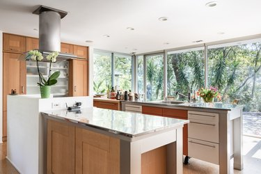 Modern kitchen with wood cabinets, steel counters, long car handles, and full-glass windows.