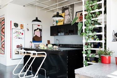 A kitchen with black cabinets, black pendant lights, curved wood stools, and a pvc pipe shelf. Decorated with art and plants.