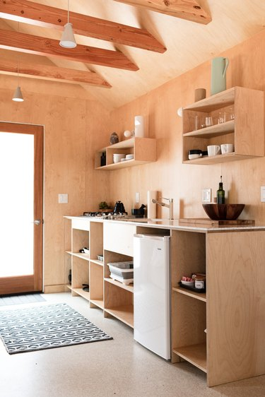 A wood-walled kitchen with wood cabinets