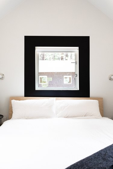 A minimalist white bedroom with a black framed window