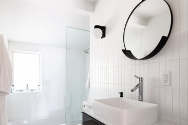 A minimalist all white tiled bathroom with a round black framed mirror
