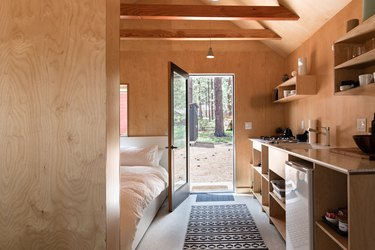 A wood cabin in the forest with a minimalist bedroom and wood walls and shelving