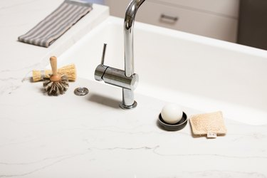 white countertop and chrome faucet and dish brush