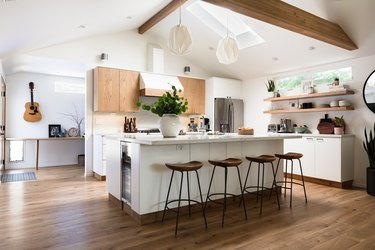 wooden upper kitchen cabinets and lower white kitchen cabinets and modern bar stools with white island and open shelving and wood floors